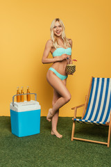cheerful girl holding cocktail in half of fresh pinapple near deck chair and portable fridge on yellow background