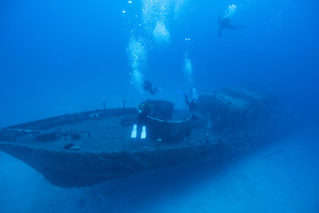 Photo sur Plexiglas Naufrage High Angle View Of Scuba Divers Swimming Over Ship Wreck Undersea