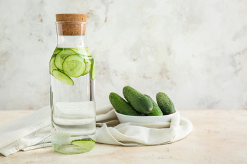 Fotobehang - Bottle of infused cucumber water on light background