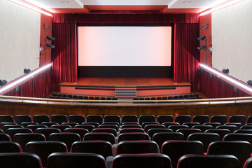 Inside of movie theatre with empty seats and stage Fotomurales