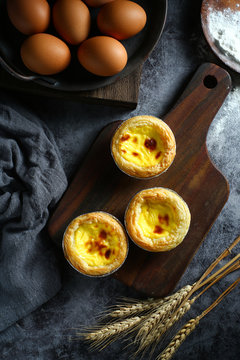 egg tarts on wooden board on dark background