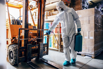 Man in protective suit and mask disinfecting forklift in warehouse from corona virus / covid-19.