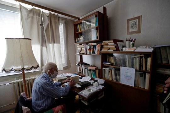 Petr Brandejsky, a 90-year-old Holocaust survivor, reads a book at his apartment in Prague