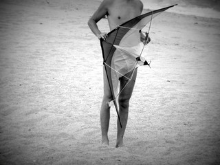Cropped Image Of Man Holding Kite While Standing On Sand At Beach