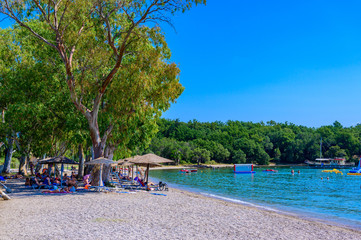 Wall Mural - Dassia Beach with crystal clear azure water in beautiful landscape scnery - paradise coastline of Corfu island, Ionian archipelago, Greece.