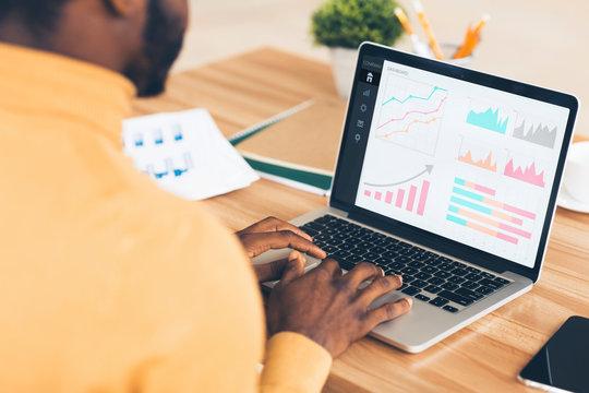 Black entrepreneur analyzing graph on laptop at workplace