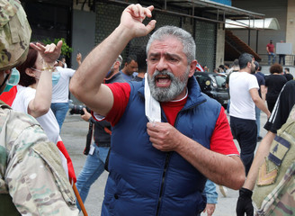 A Lebanese demonstrator gestures during a protest against the collapsing Lebanese pound currency and the price hikes, in Zouk