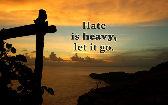 Inspirational quote - Hate is heavy, let it go.. On natural abstract background of dramatic colorful sunset sky clouds over the ocean, with land, wild plants & wooden fence silhouette.