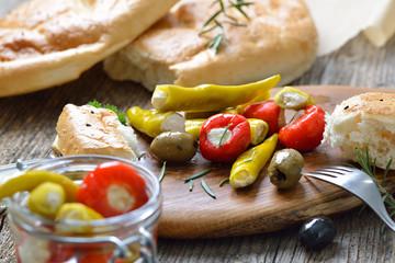 Griechischer Imbiss bestehend aus Oliven sowie Peperoni und Kirschpaprikas gefüllt mit Frischkäse, dazu Fladenbrot – Greek snack, cherry peppers and pepperoni stuffed with cream cheese, served with pi
