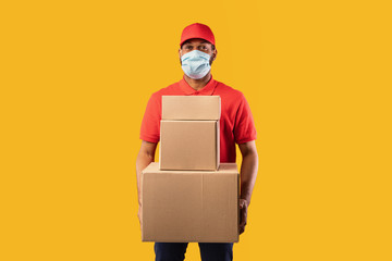 African Courier Holding Boxes Posing On Yellow Background Wearing Mask
