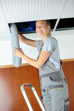woman fitting ventilation hose into roof space