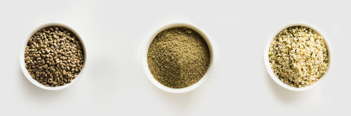 Organic dried hemp seeds, flour, kernels in white bowls isolated on white. View from above.