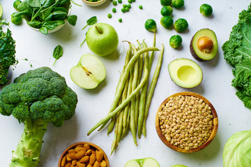 Creative flat lay with healthy vegetarian meal ingredients. Raw food concept. A variety of organic fruits, nuts, grains and vegetables with avocado. Vegan menu.