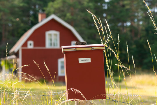 Post box with name tag (free space for your own text) in front of typical red wooden house in the countryside in Sweden.