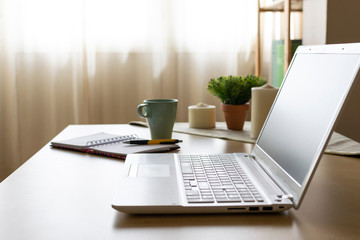 Picture of a welcoming environment of a home office desk with laptop, papers and a cup of coffee and some candles in the background. Telecommuting vibes.