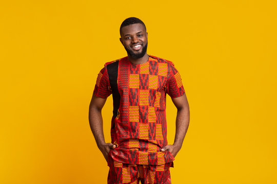 African guy in authentic clothes posing over yellow background