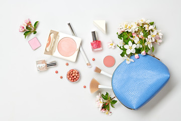 Beauty cosmetics makeup product flying. Woman make up, brushes lipstick and blossom falling in cosmetic bag. Creative fashion concept. Cosmetology make-up set fly, levitation.