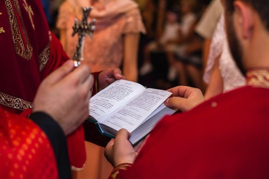 Midsection Of Priest Reading Bible At Church