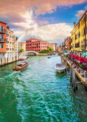 Venice cityscape at sunset time, Italy. Cannaregio canal street view with two beautiful bridges, lot of boats and restaurants. Calle de la Cereria Dorsoduro district renowned place.