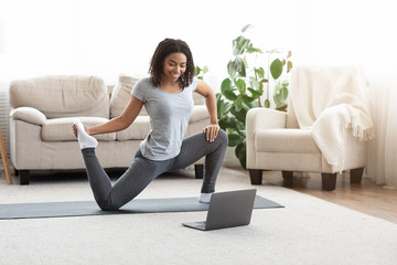 Training On Isolation. Sporty Woman Practicing Yoga In Front Of Laptop