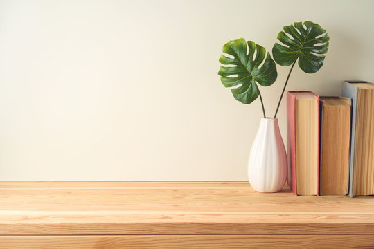 Books and plant on wooden table with copy space. Education background