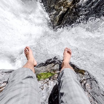 Low Section Of Man Sitting On Edge Against Waterfall