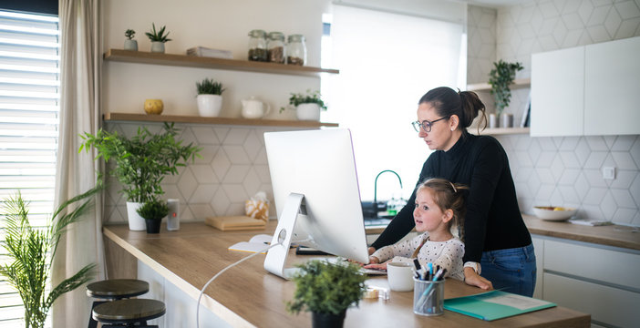 Woman with small daughter working indoors at home office.
