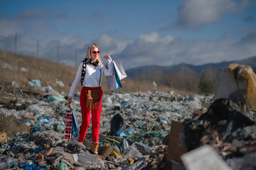 Modern woman on landfill, consumerism versus pollution concept. Wall mural