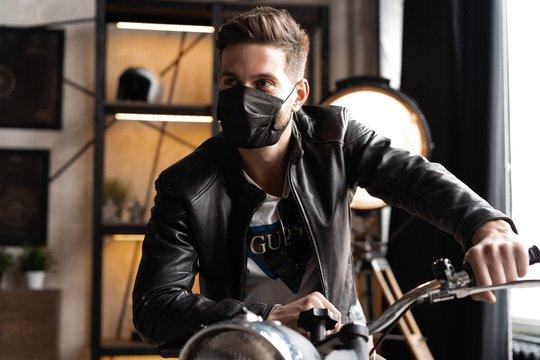 Handsome brutal male biker in black mask in leather jacket sitting on motorcycle looking forward.