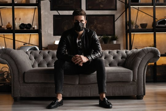 Handsome young manin black mask. Fashionable man in leather jacket standing and looking at window