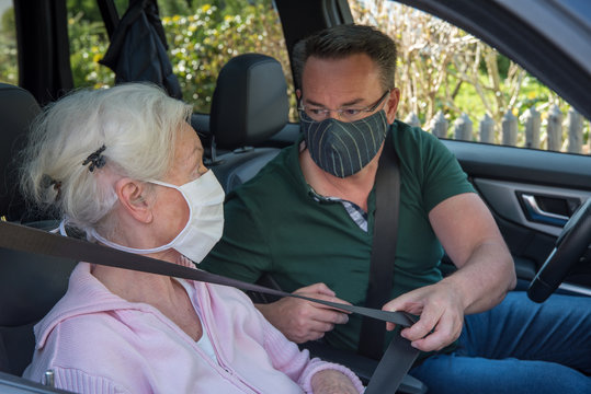 Mother and son with face masks together in the car