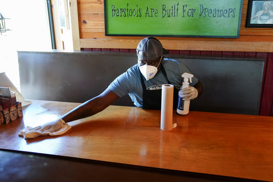 Rico Forde cleans a table after a group of patrons at lunch on it at Moe's Original BBQ after it reopened to the public as part of the phased reopening of businesses from the coronavirus disease rules in Atlanta