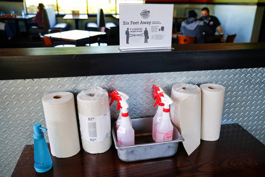 A box of cleaning supplies and a message about social distancing are seen at Bad Daddy's Burger Bar on the day restaurants and theaters were allowed to reopen to the public as part of the phased reopening of businesses and restaurants in Smyrna
