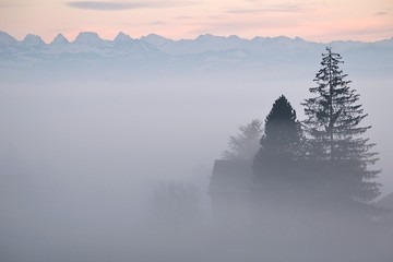 Scenic View Of Sea In Front Of Mountains In Foggy Weather