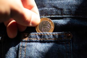 Dedo segurando uma moeda de 1 real brasileira no bolso da calça jeans azul masculina - Empobrecimento da População - Moeda desvalorizada
