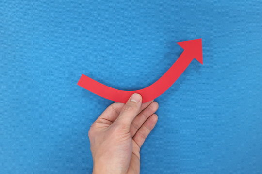 Hand holding a red arrow going up. Economy rebound, bounce back and recovery concept.