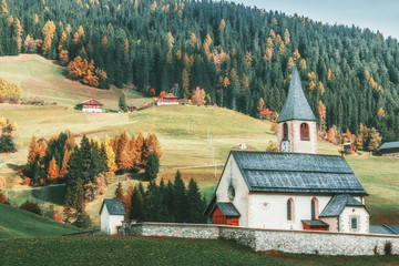 Fototapete - Traditional view of Tyrol countryside in Italian Dolomite Alps. Typical rural architecture of Austria and Italy, integrated in Alpine green hills at seasonal autumnal yellow-red forest background.