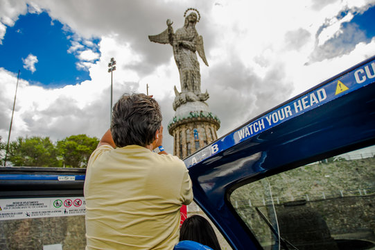 QUITO, ECUADOR - SEPTEMBER 10, 2017: Unidentifed woman taking pictures of panecillo statue and enjoying the beautiful view from touristic bus around different touristic places in the city of Quito in