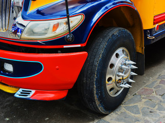 Front corner of a colorful bus in Nicaragua showing chrome spikes on wheel hub.