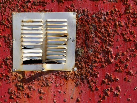 Air Duct On Weathered Red Wall During Sunny Day