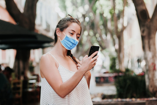 Latin Woman wearing hygienic mask to prevent infection or respiratory illness and holding a smartphone. Mexican girl with Protection against contagious disease, coronavirus in Mexico Latin America