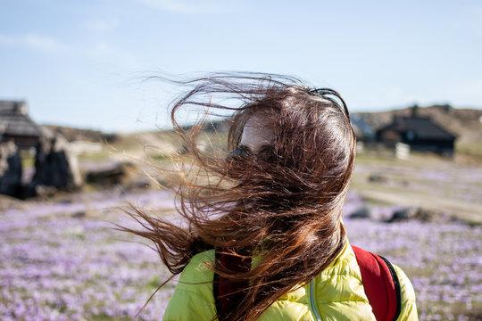 young beautiful woman walking outside windy day