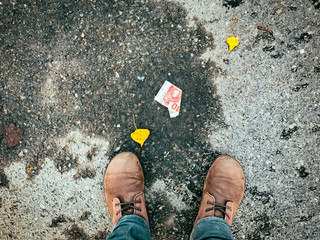 Low Section Of Man Standing By Fallen Paper Money On Road