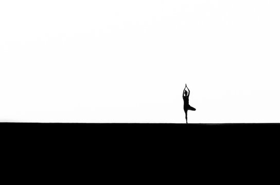 Silhouette Woman Practicing Tree Pose Against White Background
