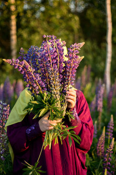 Muslim woman in a yellow scarf and in a purple dress stands on a field of lupins. Summer day. Sunset. Islam. Ramadan in the spring.
