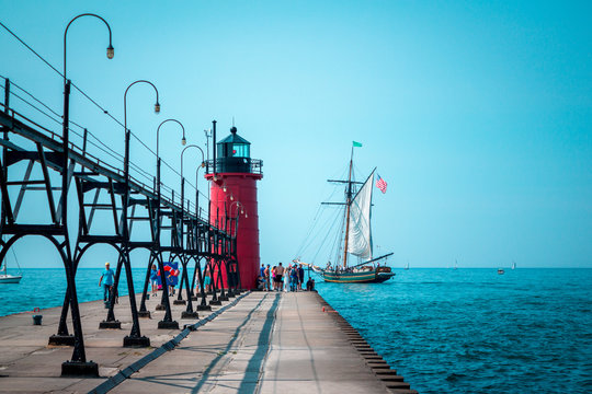 Tall ship sailing past a lighthouse on a summer day in South Haven