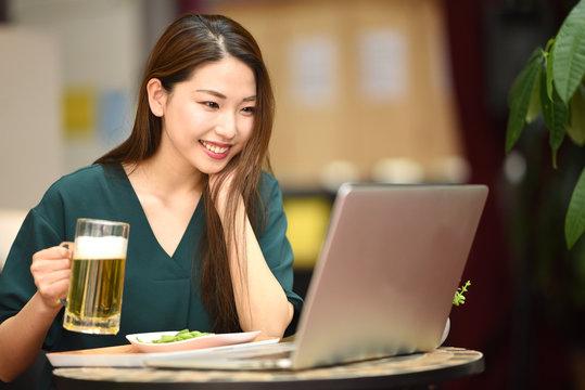 PCを見ながらお酒を飲む女性