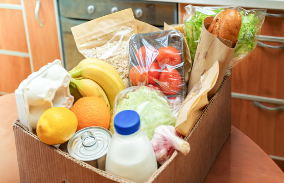Close-up cardboard box with different fresh packed food products on kitchen table. Safe delivery. Selective focus.