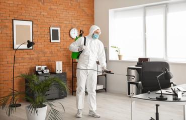 Worker in biohazard suit disinfecting office