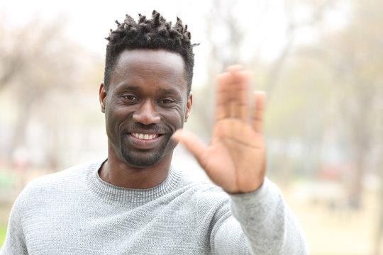 Happy black man waving hand looking camera